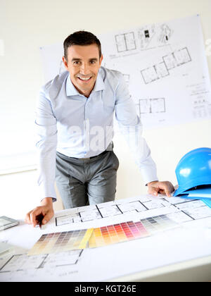 Smiling architect leaning on desk in office - Stock Photo