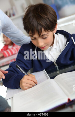 Young schoolboy sitting in classroom - Stock Photo