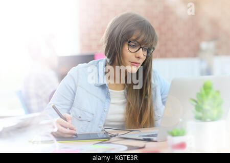 Young woman working with graphic tablet in office - Stock Photo