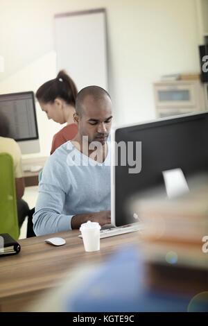Man working on desktop computer - Stock Photo