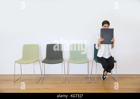 Woman in waiting room for job interview being anxious - Stock Photo