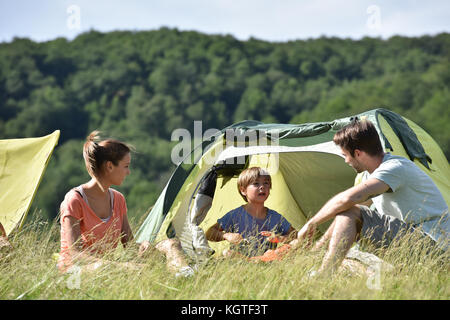 Family of four in camp tent - Stock Photo