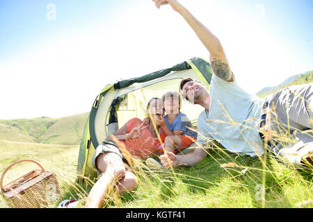 Family taking selfie picture while camping - Stock Photo