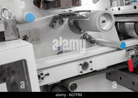 factory and equipment for the production of female sanitary napkins. women hygiene pads on a conveyor belt closeup - Stock Photo