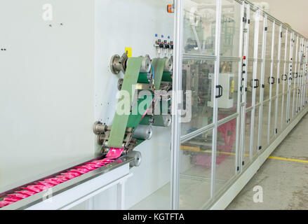 factory and equipment for the production of female sanitary napkins. - Stock Photo