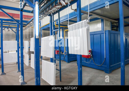 workshop for assembling and painting household heating radiators. conveyor line painting and drying of household - Stock Photo