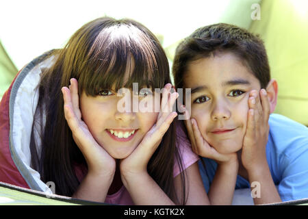 Portrait of children laying in camp tent - Stock Photo
