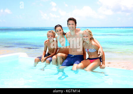 Family sitting on the side of an infinity pool - Stock Photo
