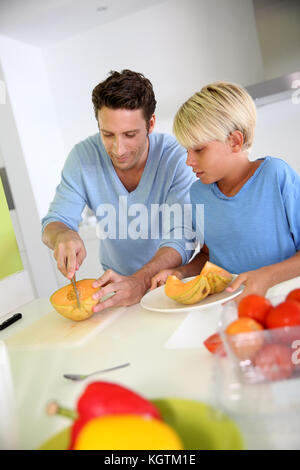 Father and child preparing melon for dinner - Stock Photo