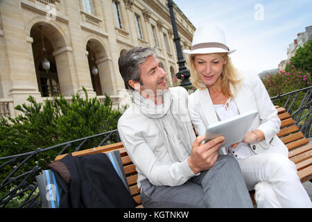 Trendy couple using electronic tablet on city bench - Stock Photo