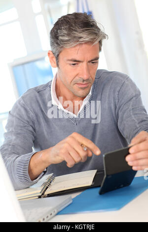 Man working in office on calculator - Stock Photo