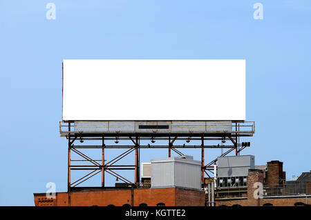 Blank billboard on rooftop against clear blue sky. Outdoor advertising in the city. - Stock Photo