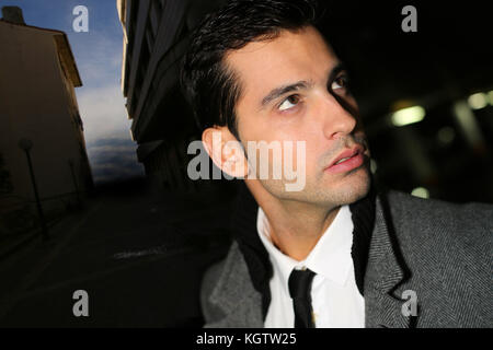 Handsome guy standing in the street by night - Stock Photo