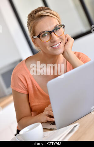 Blond woman with eyeglasses working from home with laptop - Stock Photo