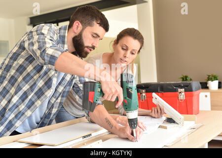 Couple assembling new furniture - Stock Photo