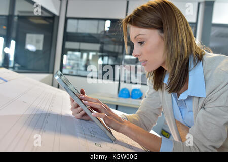 Woman engineer working on digital tablet - Stock Photo