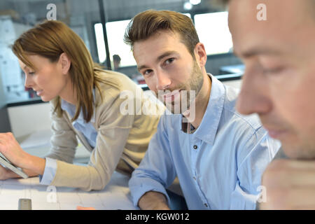 Portrait of architect amongst group in meeting - Stock Photo