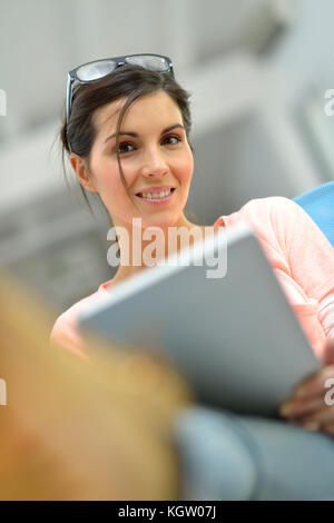 Young woman in office working on tablet - Stock Photo
