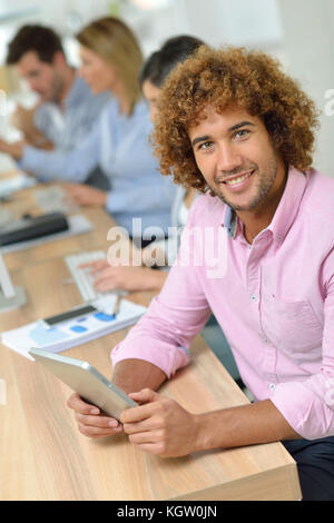 Young businessman in office working on tablet - Stock Photo