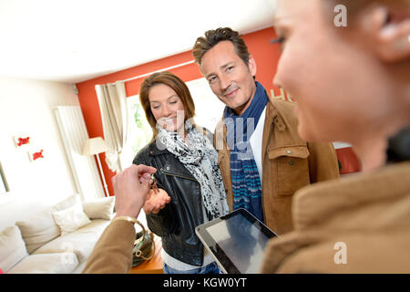 Real estate agent giving house keys to clients - Stock Photo