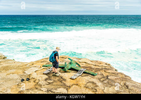 A tourist admires Stephen Harrison's artwork entitled 'Molly and Charles' during the 2017 Sculptures by the Sea - Stock Photo