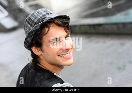 Portrait of cheerful young man standing in street - Stock Photo