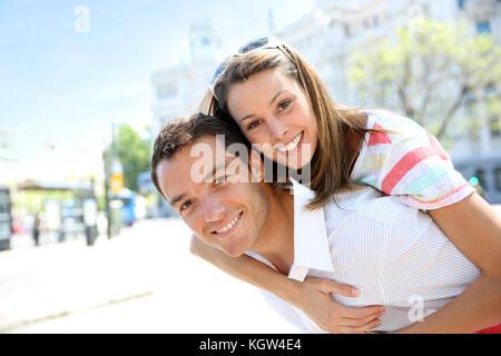 Man giving piggyback ride to girlfriend - Stock Photo