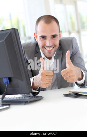 Happy businessman showing thumbs up - Stock Photo
