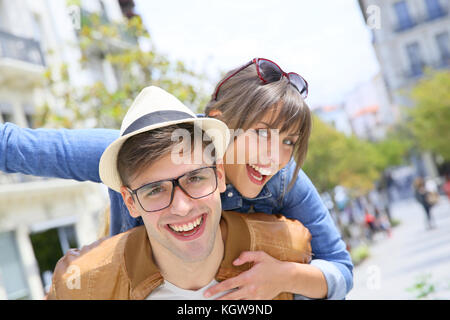 Man giving piggyback ride to girlfriend in the street - Stock Photo