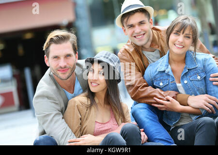 Group of young people hanging out together in town - Stock Photo