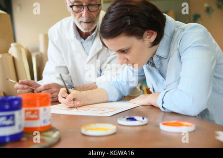 Young woman at school studying decorative painting - Stock Photo