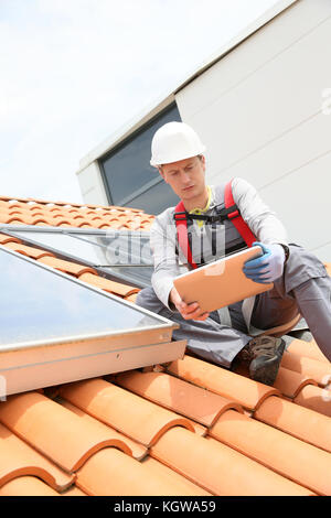 Man on roof top checking on solar panel installation - Stock Photo