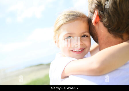 Portrait of cute little girl held in father's arms - Stock Photo