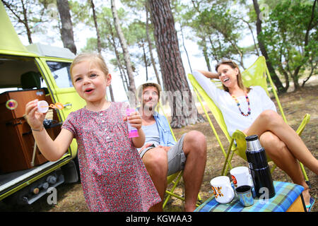 Little girl blowing soap bubbles, parents in background - Stock Photo