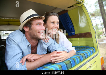 Cheerful young couple laying on a camper van - Stock Photo