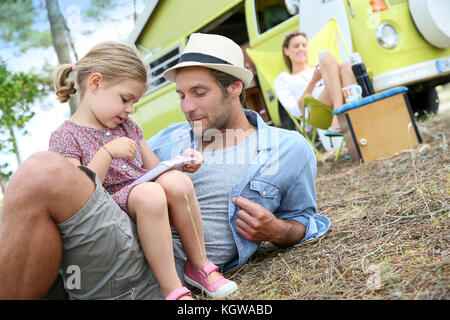 Daddy with little girl playing together on campground - Stock Photo