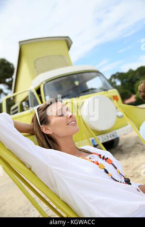 Cheerful woman relaxing in chair by camper van - Stock Photo
