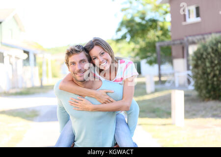 Man giving piggyback ride to woman in front of new home - Stock Photo