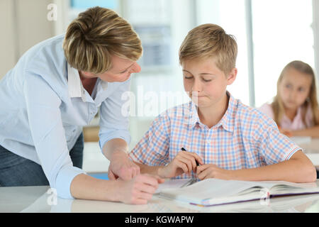 Teacher with schoolboy in classroom - Stock Photo