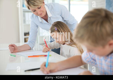 Teacher helping kids in classroom - Stock Photo