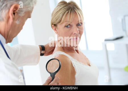 Elderly woman consulting doctor for skin control - Stock Photo
