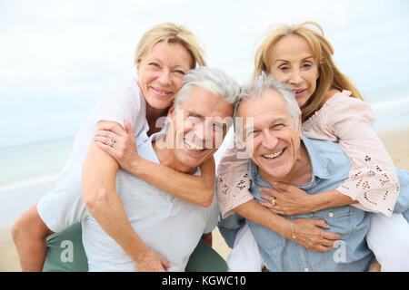 Senior men giving piggyback ride to senior women - Stock Photo