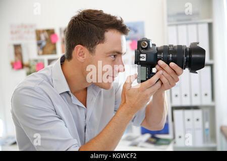 Portrait of photographer taking pictures in studio - Stock Photo