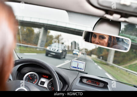 Woman in car binnacle looking at rear view mirror - Stock Photo