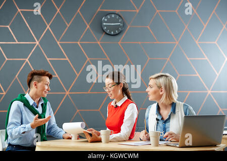 Two young journalists listening to their guest in studio and making notes - Stock Photo
