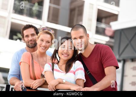 Group of young couples standing by building of apartments