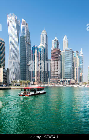 DUBAI, UAE - 31OCT2017: A Water Bus moving towards the Iconic towers of Dubai Marina including (l-r) Cayan, Damac - Stock Photo