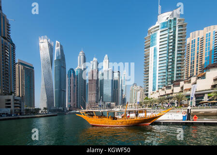 DUBAI, UAE - 31OCT2017: A dhow backed by the Iconic towers of Dubai Marina including (l-r) Cayan, Damac Heights, - Stock Photo