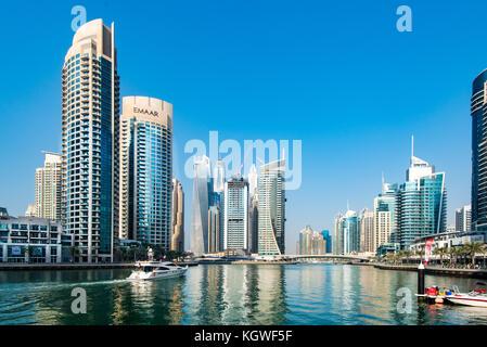 DUBAI, UAE - 31OCT2017: A motor yacht moving past Park Island and towards the iconic towers of Dubai Marina. - Stock Photo