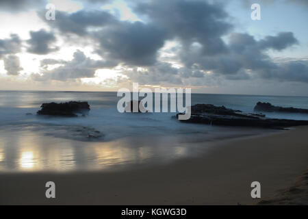 The sun rises over Sandy Beach, on the Southeast side of Oahu, Hawaii - Stock Photo